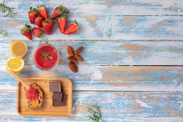 Mermelada de fresa sobre fondo de madera Foto Premium