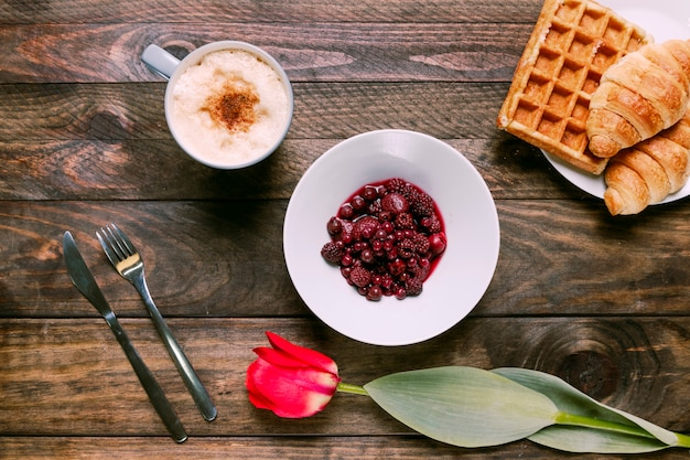 Mermelada en tazón, flor fresca, panadería, cubertería y taza de bebida Foto gratis