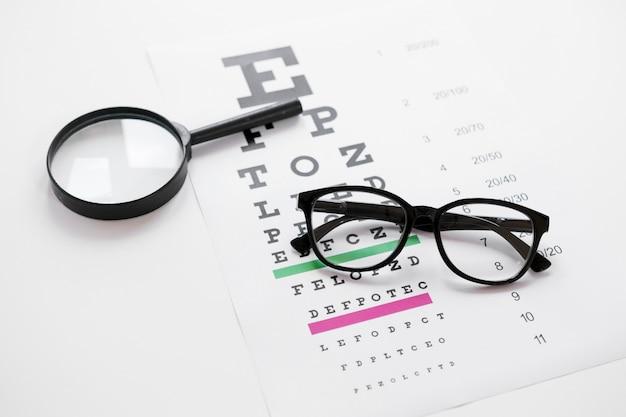 Mesa de alfabeto de alto ángulo con lupa y gafas Foto gratis