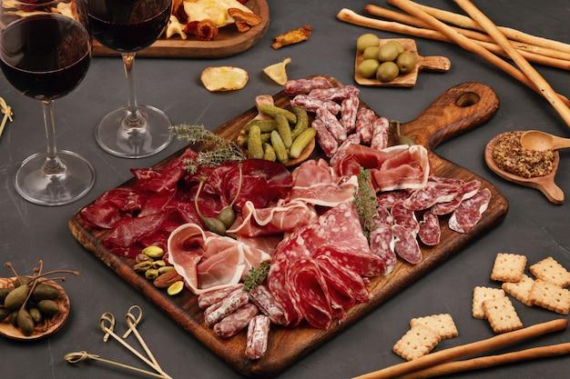Mesa de aperitivos con diferentes antipasti, queso, embutidos, snacks y vino. salchicha, jamón, tapas, aceitunas, queso y galletas para fiesta buffet. Foto Premium