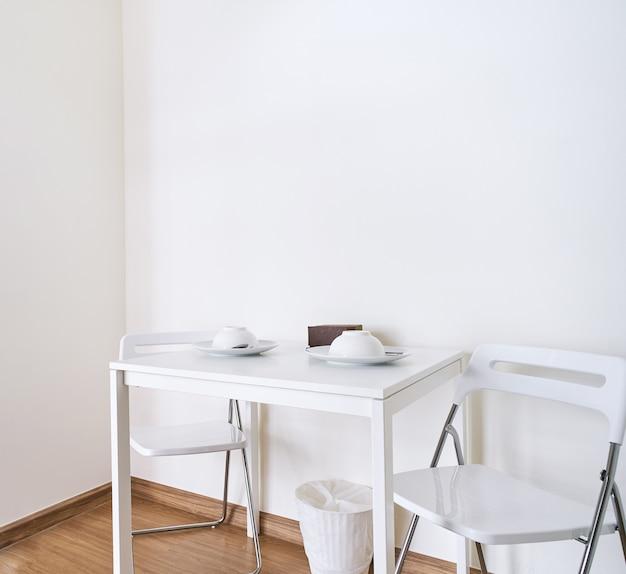Mesa blanca con sillas plegables en la sala de cocina ...