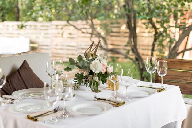 Mesa de boda decorada con flores frescas en un jarrón de latón. boda floristería. mesa de banquete para invitados al aire libre con vistas a la naturaleza verde. ramo con rosas, hojas de eustoma y eucalipto Foto Premium