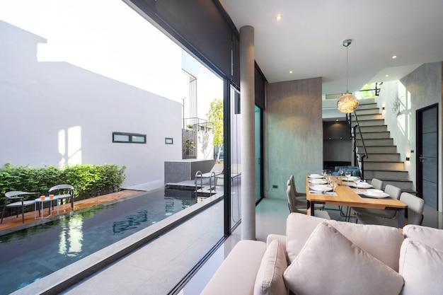 Mesa de comedor con diseño tipo loft y espacio abierto para acceder a la piscina. Foto Premium