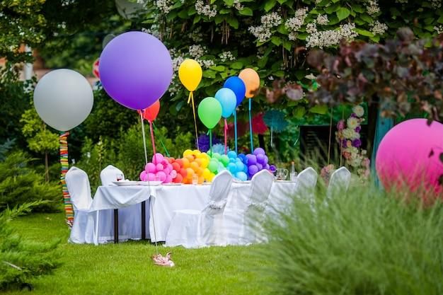 Mesa de cumpleaños con globos arcoiris. vacaciones de verano en el parque. Foto Premium