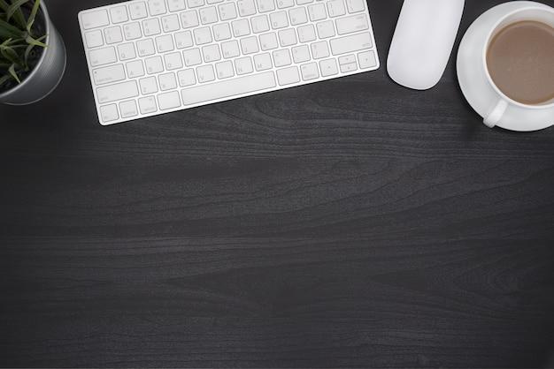 mesa de escritorio de oficina negro con ordenador y taza