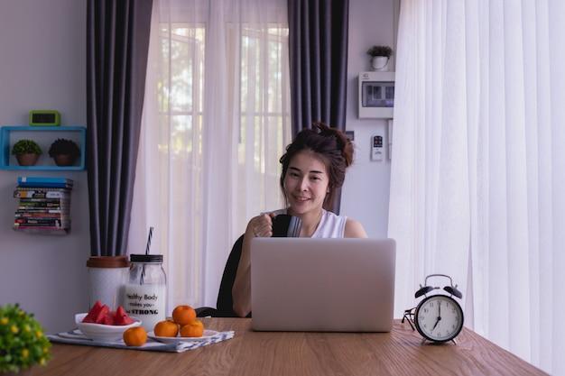 Mesa de desayuno con el café asiático joven del dink de la mujer, trabajadora por mañana. Foto Premium