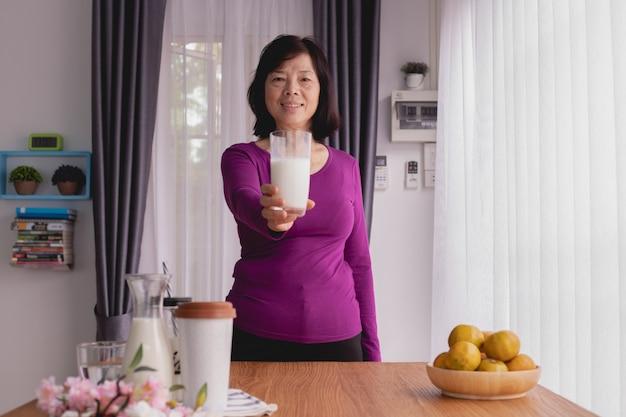 La mesa de desayuno con la mujer mayor asiática sostiene el vidrio de leche en casa. Foto Premium