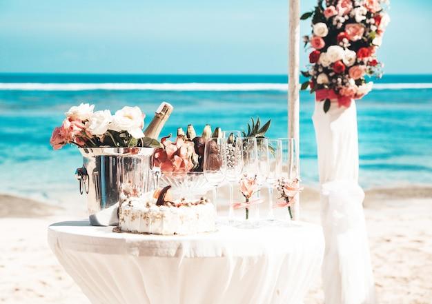 Mesa elegante de boda con frutas tropicales y pastel en la playa Foto gratis