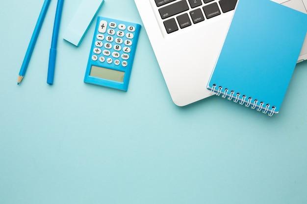 Mesa de escritorio de oficina con computadora portátil, cuaderno, lápiz, borrador, calculadora. endecha plana Foto Premium