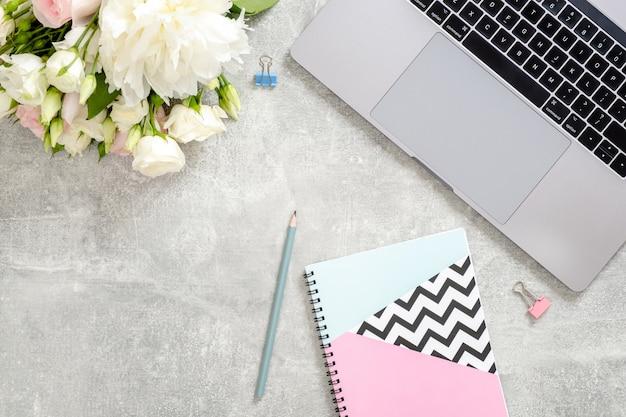Mesa de escritorio de oficina para mujer con computadora portátil, flores, elegante bloc de notas diario, papelería en piedra de hormigón Foto Premium