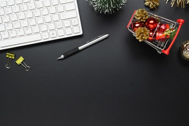 Mesa de escritorio de oficina negra con adornos navideños en carrito de compras Foto Premium