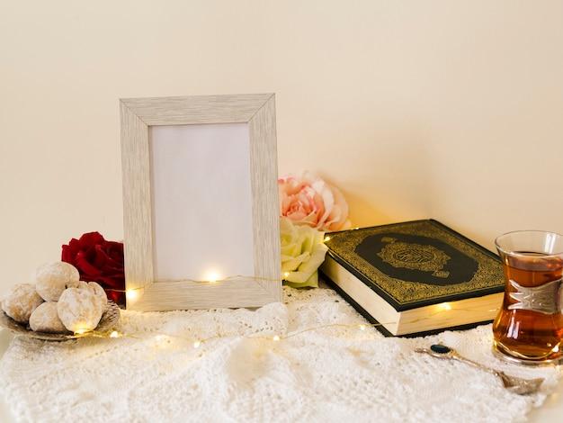 Mesa festiva con quran y marco de fotos. Foto gratis