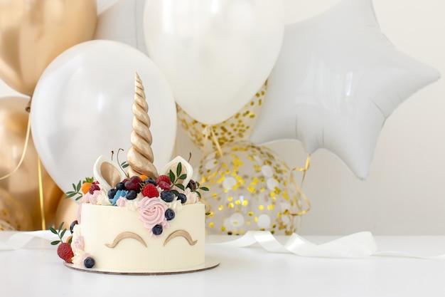 Mesa de fiesta de cumpleaños con pastel de unicornio Foto Premium