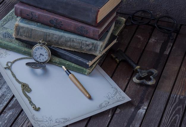 En la mesa hay libros antiguos, relojes de bolsillo, estilográfica, gafas y papel de escribir. Foto Premium
