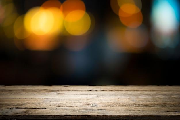 Mesa de madera vacía de plataforma y bokeh por la noche. Foto Premium