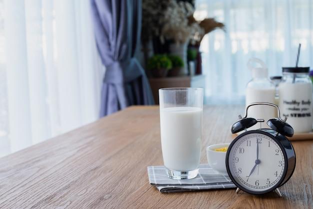 Mesa de madera con vaso de leche y despertador retro en la sala. Foto Premium