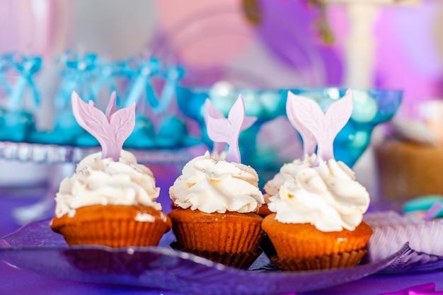 Mesa para niños con cupcakes con cobertura blanca decorada con cola de sirena morada. Foto Premium