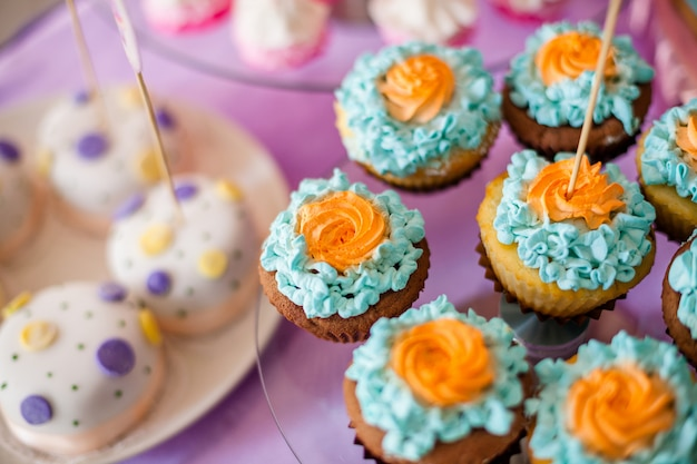 Mesa para niños con cupcakes con tapa azul y naranja y elementos decorativos en rosa y azul brillante Foto Premium