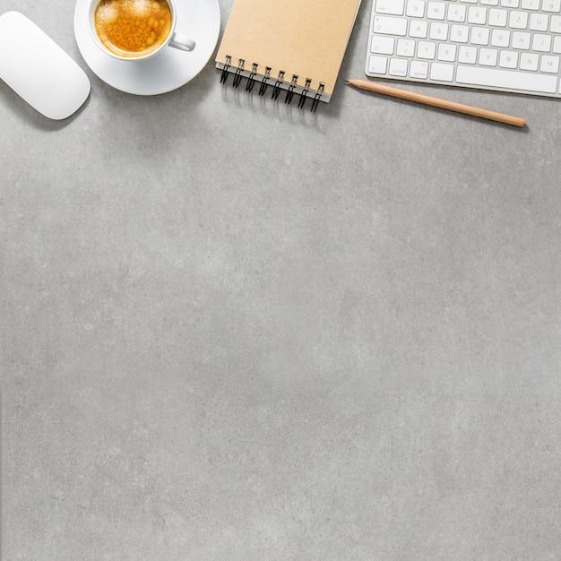 Mesa de oficina con taza de café, teclado y bloc de notas Foto gratis