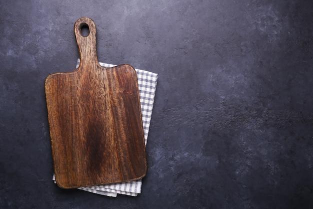 Mesa de piedra oscura con tabla de cortar y servilleta de lino. espacio de copia Foto Premium