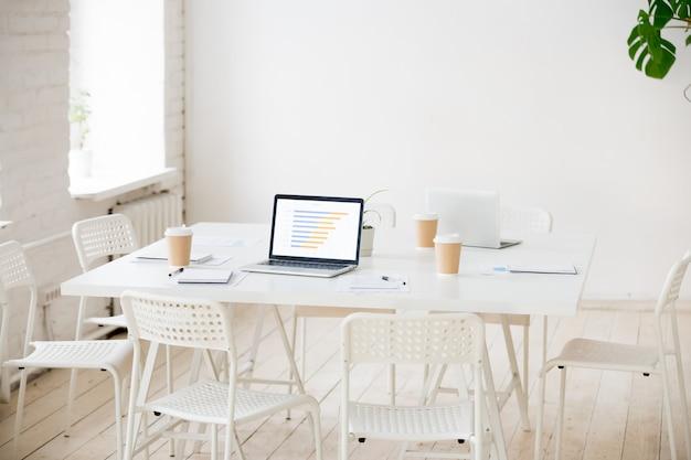 Mesa de reuniones con computadoras portátiles y café en la oficina vacía. Foto gratis