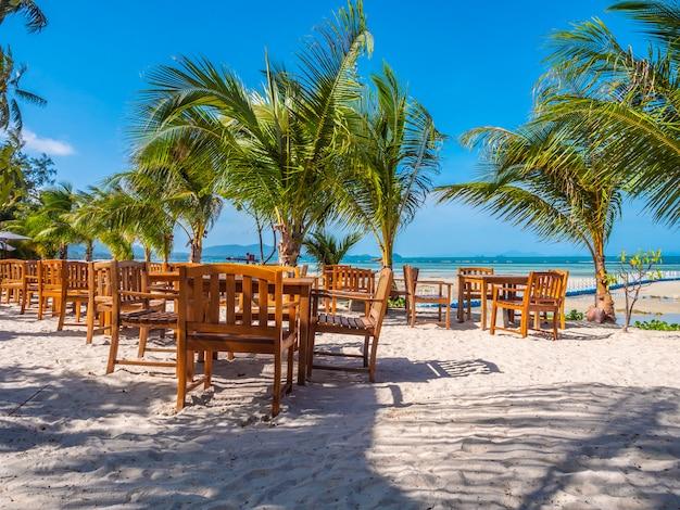 Mesa y silla de madera en la playa. Foto gratis