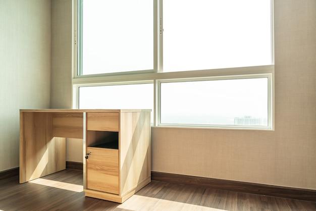 Mesa de trabajo vacía en la habitación con ventana Foto Premium