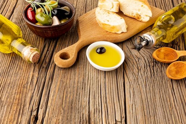Mezcla de aceitunas de pan de alto ángulo y botellas de aceite Foto gratis