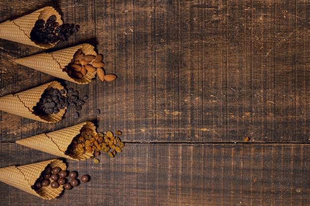 Mezcla de aperitivos dulces en conos. Foto gratis