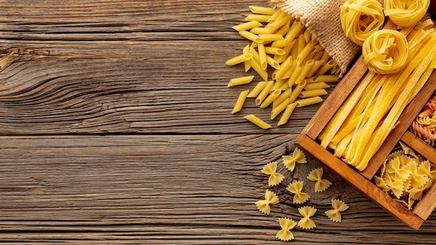 Mezcla de pasta cruda en caja de madera sobre la mesa Foto gratis