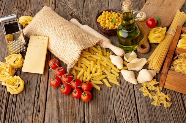 Mezcla de pasta cruda con tomate, aceite de oliva y queso duro. Foto gratis
