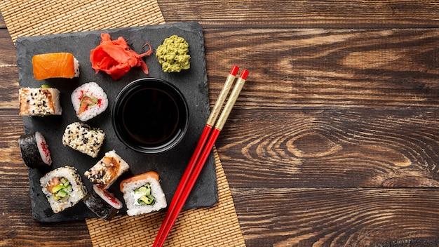 Mezcla plana de rollos de sushi maki y palillos con espacio de copia Foto gratis