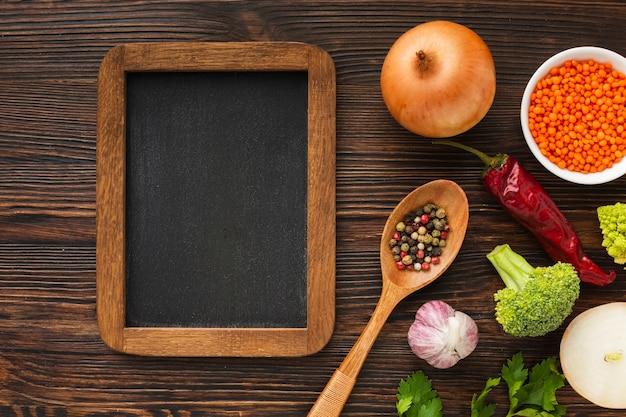 Mezcla de verduras planas y pizarra en blanco Foto gratis