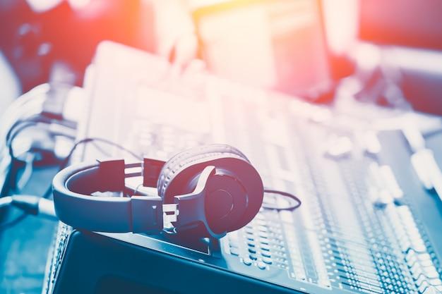 Mezclador de sonido con auriculares ingeniero de mezcla musical concepto fondo azul vintage color Foto Premium