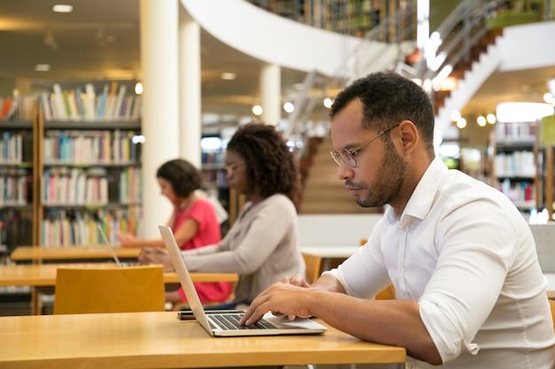 Mezcle a los alumnos que corren trabajando en la computadora en una biblioteca pública Foto gratis