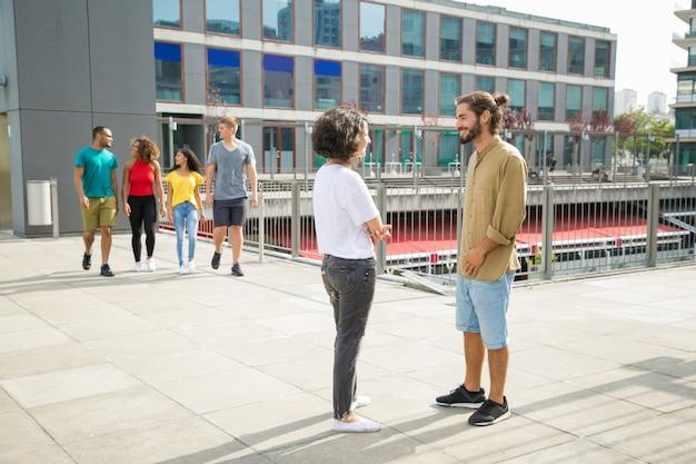 Mezcle a los estudiantes que corren caminando por el campus universitario Foto gratis