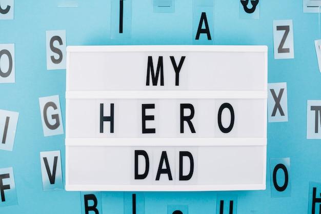 Mi héroe papá título en la tableta cerca de letras Foto gratis