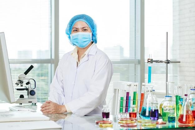 Microbiólogo asiático confiado que presenta para la fotografía Foto gratis