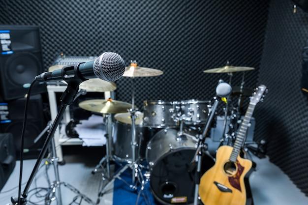 Micrófono de condensador profesional de estudio, concepto musical. grabación, micrófono de enfoque selectivo en estudio de radio, micrófono de enfoque selectivo y guitarra de equipo musical borroso, Foto Premium