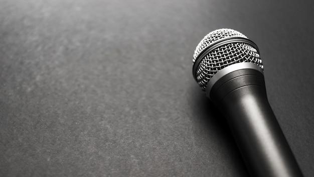 Micrófono negro y plateado sobre un fondo negro Foto gratis