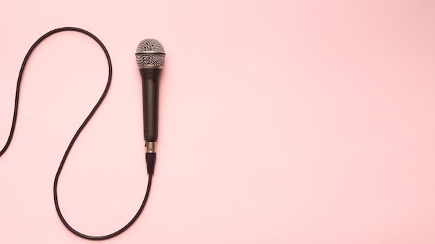 Micrófono negro y plateado sobre un fondo rosa Foto gratis