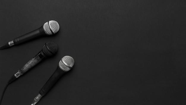 Micrófonos negros y plateados sobre un fondo negro Foto gratis