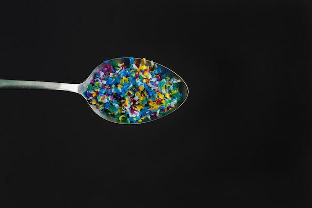 Microplástico de color en cuchara sobre fondo negro Foto Premium