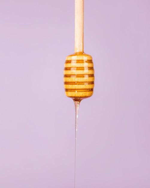 Miel goteando de un cucharón de madera sobre fondo morado Foto gratis