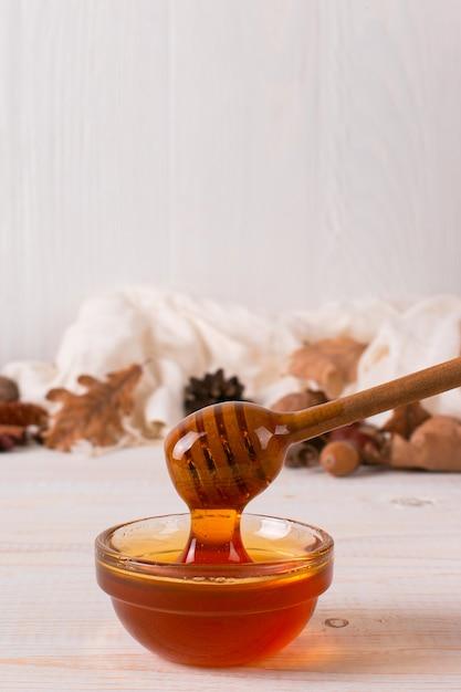 Miel, palo, frasco, bufanda, hojas secas. foto rústica del otoño dulce, fondo de madera blanco, copyspace. Foto Premium