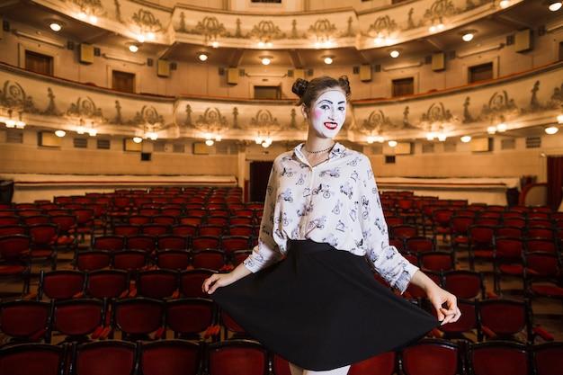 Mime femenino de pie en un auditorio posando Foto gratis