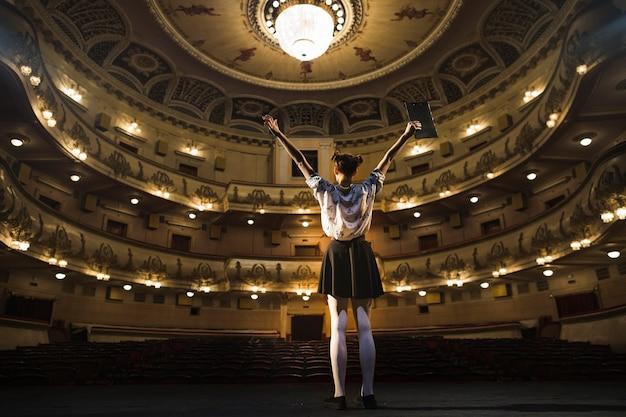 Mime femenino de pie en el escenario levantando los brazos Foto gratis