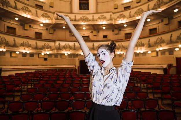 Mime femenino que se coloca en un auditorio que levanta sus brazos Foto gratis