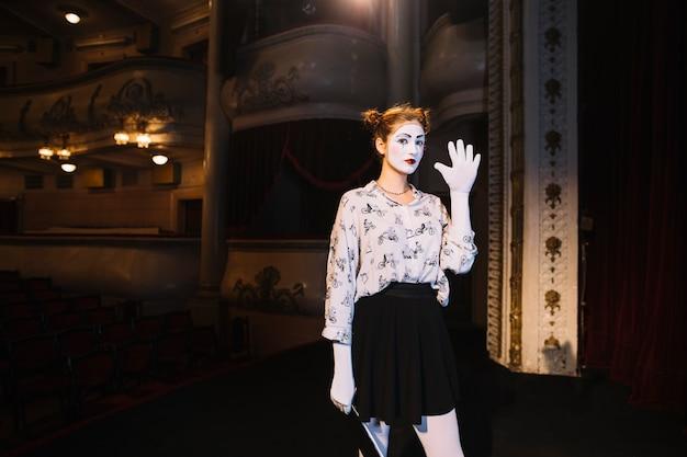 Mime femenino que se coloca en el escenario que muestra su palma Foto gratis