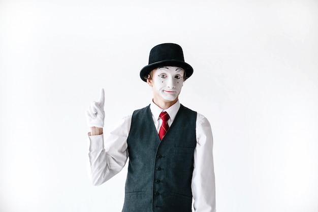 Mimo divertido en sombrero negro sostiene su dedo hacia arriba Foto gratis